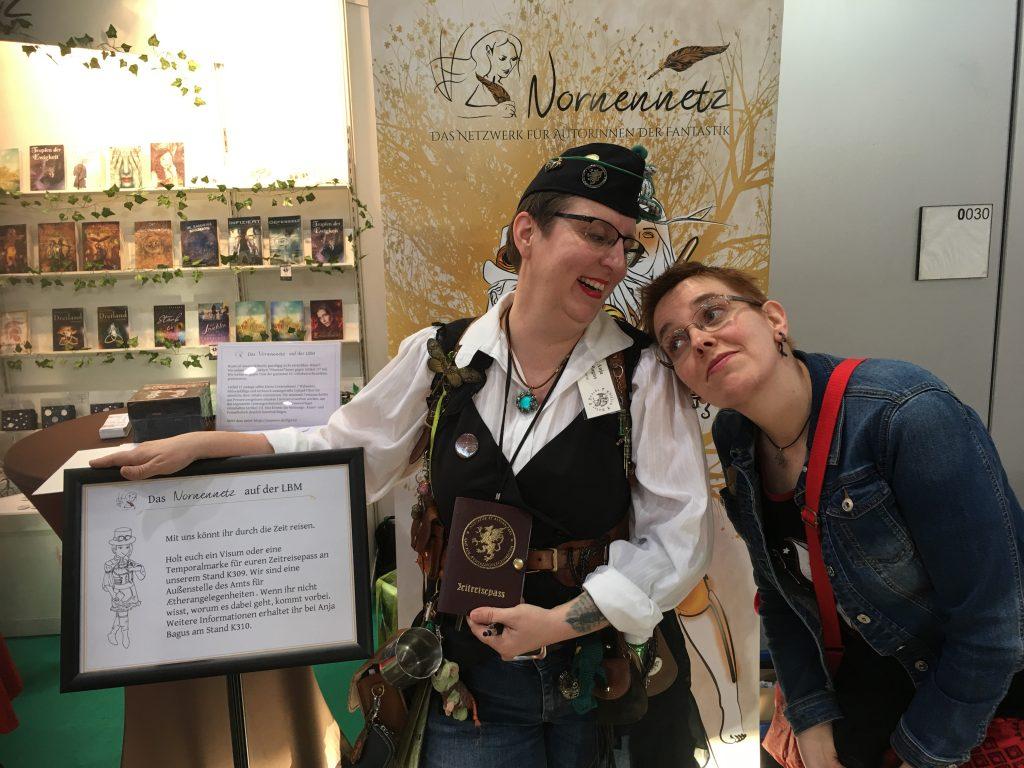 Zwei Frauen in lustiger Pose vor dem Messestand des Nornnennetz.