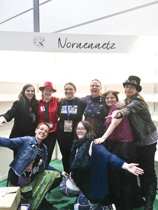 Im Hintergrund befindet sich ein leerer Messestand. Davor posieren mehrere Autorinnen.