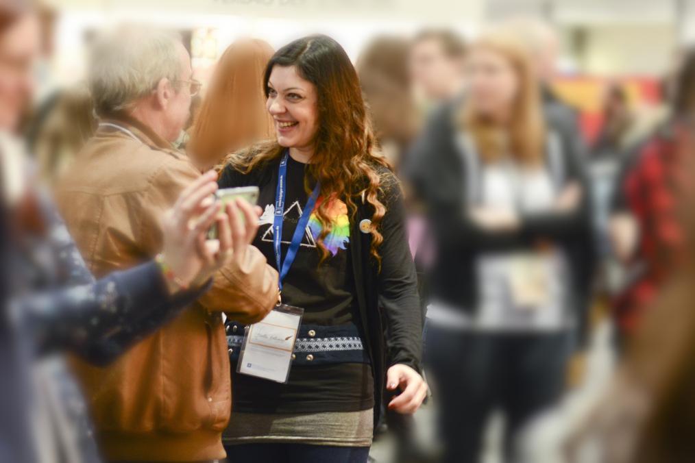Im Vordergrund ist die freundlich dreinblickende Autorin Stella Delaney im Gespräch mit einem Herren zu sehen. Im Hintergrund stehen und laufen Messebesucher.